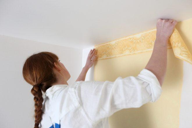 Frau mit braunen Haaren und Zopf bringt eine gelbliche Tapete an einer weißen Wand an.